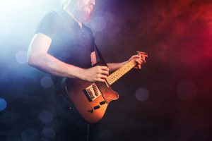 A fashionable young man with long hair and beard plays a black electric guitar at a live music venue, orange and blue stage lights illuminating the scene. Focus on the guitar. Horizontal image with copy space.
